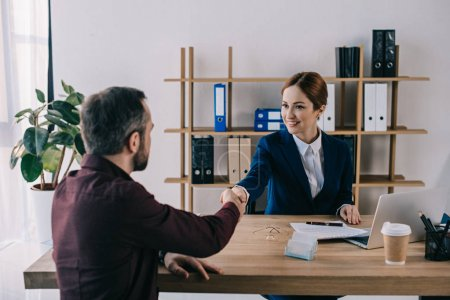 smiling businesswoman and client shaking hands on meeting in office