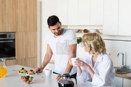 Photo pour Heureux jeune couple regardant les uns les autres tout en prenant son petit déjeuner ensemble - image libre de droit