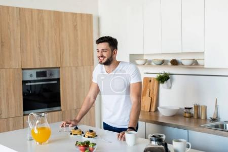Photo for Smiling young man leaning at kitchen table with breakfast and looking away - Royalty Free Image