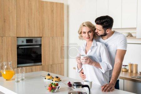 Photo pour Jeune homme embrassant petite amie tenant tasse de café et regardant la caméra dans la cuisine - image libre de droit
