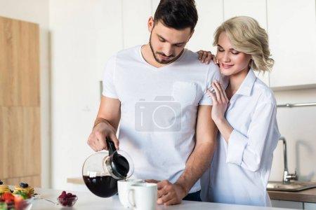Photo pour Sourire copain beau étreindre de jeune femme pendant qu'il verse le café dans la cuisine - image libre de droit