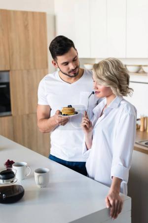 Photo pour Jeune homme tenant des crêpes et en regardant une copine sexy dans la cuisine - image libre de droit
