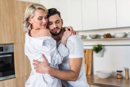 happy sensual young couple hugging in kitchen