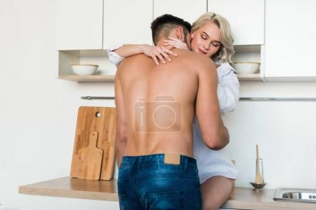 back view of shirtless young man kissing seductive girlfriend sitting on kitchen furniture