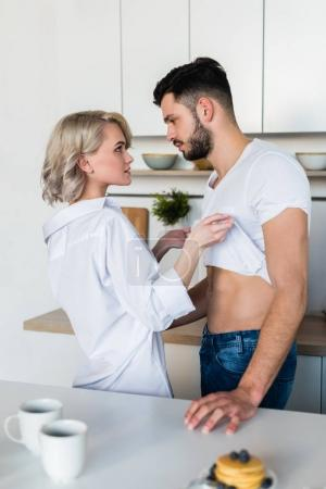 side view of seductive young couple looking at each other at morning in kitchen