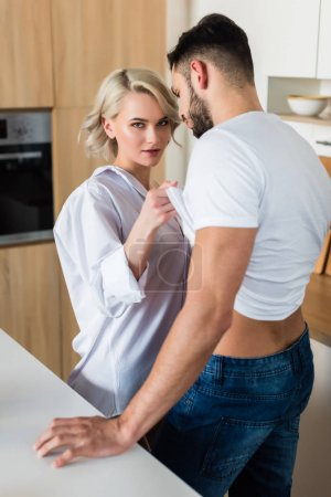 seductive young woman looking at camera and taking off t-shirt from handsome boyfriend in kitchen