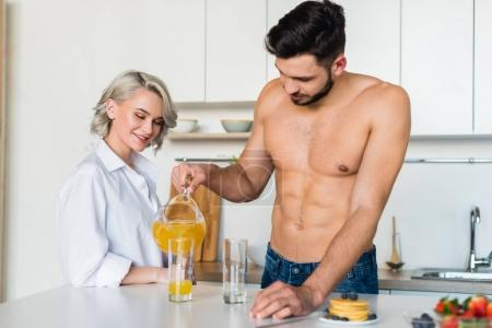 Photo for Shirtless young man pouring juice to smiling girlfriend standing near by in kitchen - Royalty Free Image