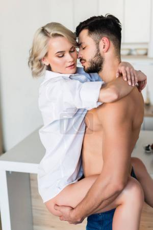 handsome shirtless young man hugging sexy girlfriend in kitchen