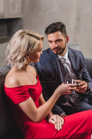 seductive stylish young couple holding glasses of red wine and looking at each other
