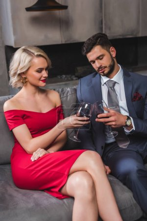 beautiful stylish young couple in suit and red dress drinking wine together