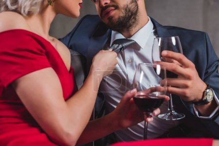 cropped shot of sexy stylish couple drinking wine together