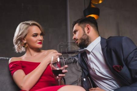 seductive young couple drinking wine, woman holding necktie of handsome boyfriend