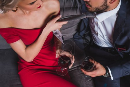 Photo for Cropped shot of fashionable couple drinking wine, woman holding necktie of handsome boyfriend - Royalty Free Image