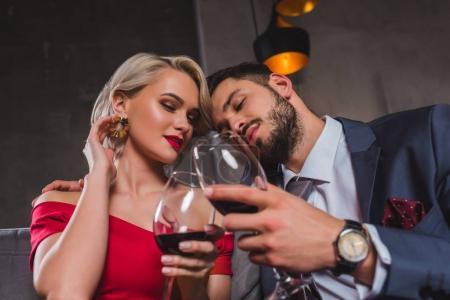 Photo pour Sensuelle jeune couple élégant ensemble boire du vin rouge - image libre de droit