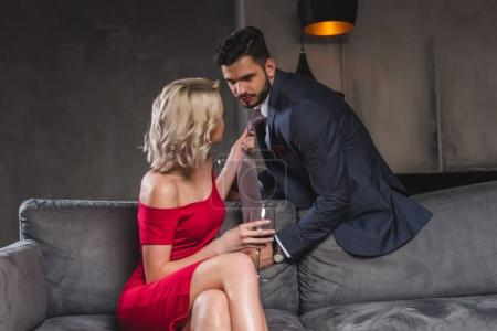 seductive stylish couple looking at each other, woman drinking wine and holding necktie of boyfriend