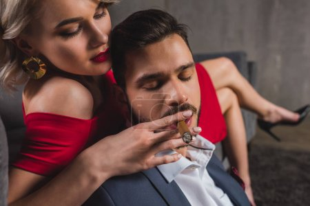 close-up view of sexy girl in red dress holding cigar while boyfriend smoking it