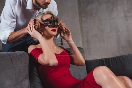 cropped shot of man putting black lace mask on seductive woman in red dress