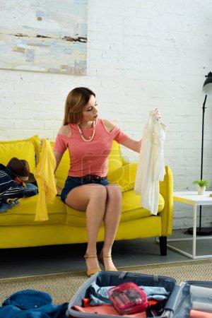 Photo pour Fille assise sur le canapé et emballage des vêtements dans le sac de voyage - image libre de droit