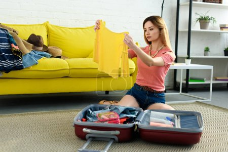 attractive girl packing summer clothes into suitcase for travel