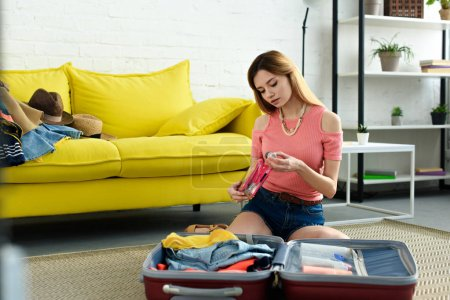 Photo for Beautiful young girl packing suitcase for travel - Royalty Free Image
