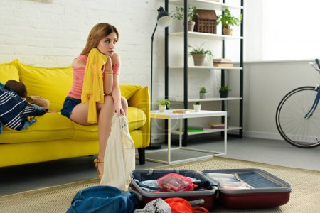 Photo for Thoughtful girl packing clothes for travel - Royalty Free Image