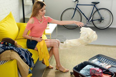 Photo pour Jeune fille jetant des vêtements dans la valise pour voyage - image libre de droit