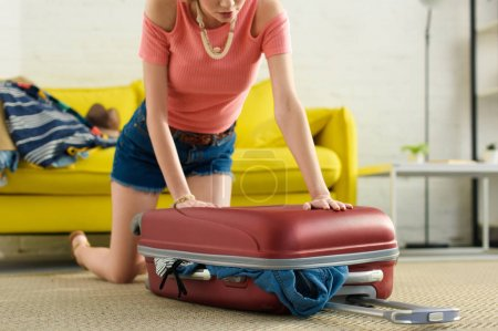 cropped view of girl packing suitcase for trip