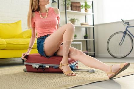 Photo pour Recadrée vue de jeune fille assise sur le sac de voyage - image libre de droit