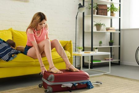 young woman packing travel bag for journey