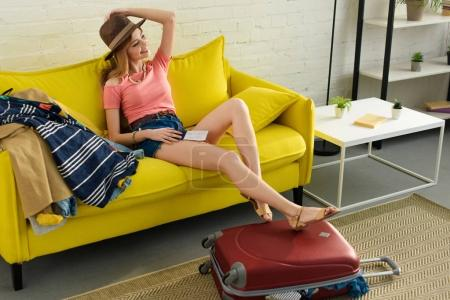beautiful happy girl in hat holding passport and air ticket while sitting on sofa with baggage
