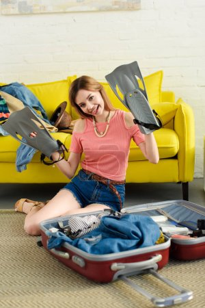 happy girl with snorkeling fins packing suitcase for travel