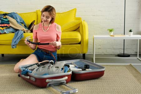 smiling girl packing snorkeling mask and fins into suitcase for travel
