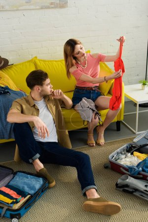 young couple packing clothes and preparing for a vacation