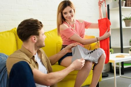 Photo for Young happy couple packing clothes and preparing for a vacation - Royalty Free Image
