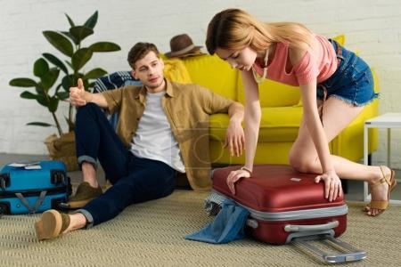 Photo pour Fille faisant ses valises et se préparant pour des vacances tout petit ami assis près - image libre de droit
