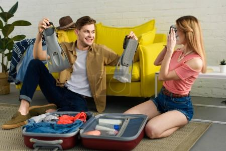 young happy couple packing fins and snorkeling mask in travel bag