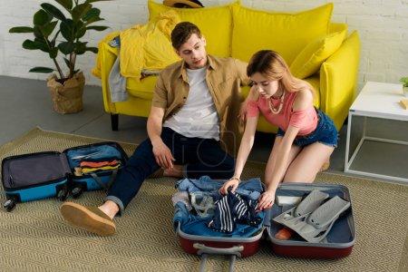 Photo pour Jeune couple valises d'emballage et la préparation des vacances ensemble - image libre de droit