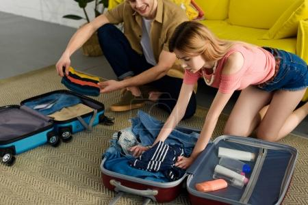 young couple packing clothes into travel bags