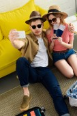 couple in sunglasses with passports and air tickets taking selfie on smartphone