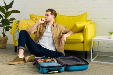 Photo for Handsome pensive man sitting on floor near sofa with travel bag - Royalty Free Image