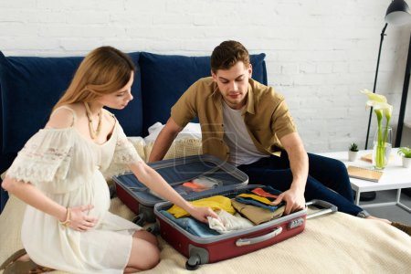 Photo for Pregnant woman and husband packing travel bag for vacation - Royalty Free Image