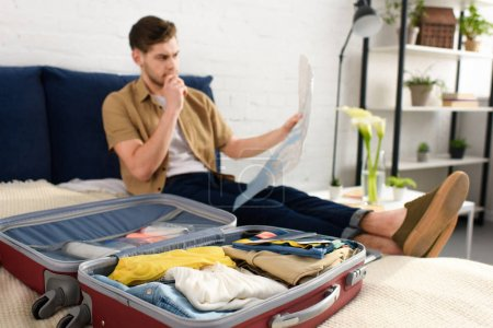 selective focus of young man looking at map while packing clothes on bed