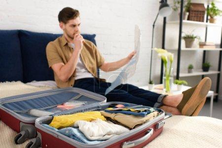 Photo pour Foyer sélectif de jeune homme regardant la carte tout en emballant des vêtements sur le lit - image libre de droit