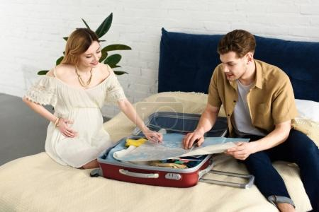 happy pregnant woman and husband looking at map and packing for vacation