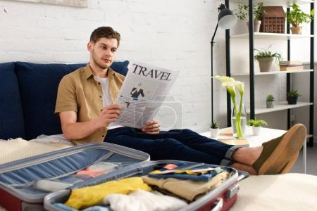 young man reading travel newspaper while packing suitcase on bed