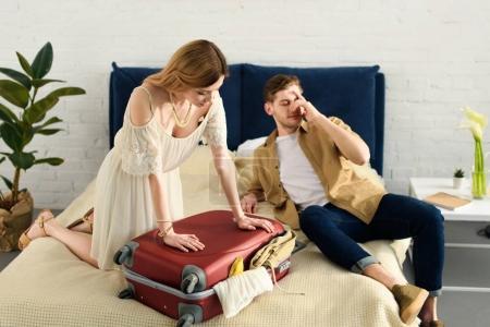 Photo pour Petite amie et petit ami emballage sac de voyage pour les vacances dans la chambre - image libre de droit