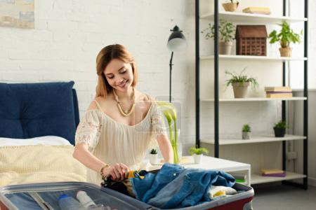 smiling girl packing clothes in travel bag for weekend