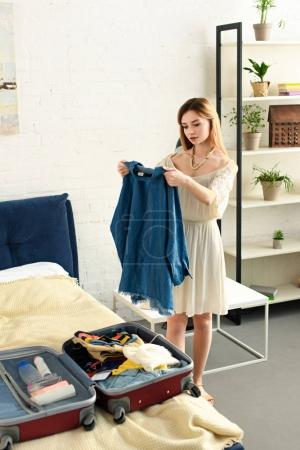 young woman packing clothes in suitcase on bed