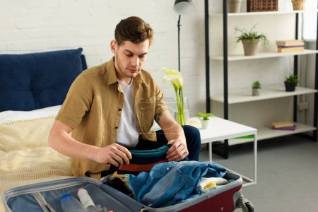 young handsome man packing luggage for vacation