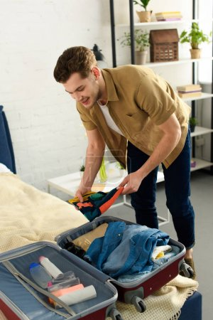 young man packing clothes into travel bag in bedroom